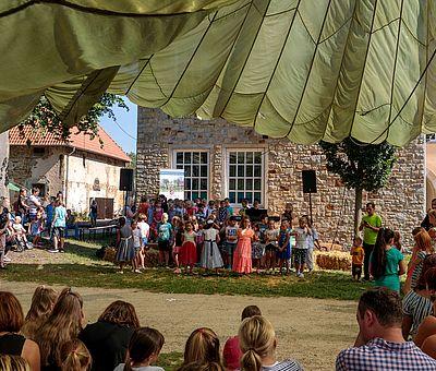 """Beim Sommerfest der Kulturen in Fürstenau im Osnabrücker Land ist einiges los. Auf diesem Bild sieht man Kinder, die schätzungsweise zwischen sechs und sieben Jahre alt sind. Sie stehen aufgereiht wie ein Chor nebeneinander und schauen zum Publikum. Rechts in diesem Kinderchor steht ein kleiner Junge, der auf einem Klavier spielt. Hinter den Kindern sieht man einen Teil eines Steinwerks und zwei Fenster des Hauses mit weißen Sprossen. Vor dem linken Fenster steht ein weißes Banner, darauf ist mit weißer Schrift auf blauem Hintergrund """"Freiwilligenagentur"""" zu lesen. Darunter ist ein Bild mit Bäumen und einer grünen Blumenwiese zu erkennen, darauf steht mit weißer Schrift geschrieben: """"Helfen macht glücklich"""". Unter der Blumenwiese ist das Wappen von Fürstenau zu erkennen. Das Wappen ist rot und darauf ist eine graue Burg zu erkennen. Unter dem Wappen ist das Banner weiß und mit schwarzer Schrift steht geschrieben: Samtgemeinde Fürstenau. Rechts und links neben den Kindern steht jeweils ein schwarzer Lautsprecher. Links neben dem Steinwerk ist noch ein weiteres Haus zu erkennen. Dies ist aber deutlich kleiner und man sieht das Dach mit roten Dachpfannen. Vor dem kleineren Haus sieht man eine Familie stehen, ein kleiner Junge sitzt im Kinderwagen und dahinter stehen weitere Kinder. Das Foto ist aus dem Publikum gemacht worden. In der ersten Reihe sieht man Kinder und Eltern zur Bühne schauen. Im Bild sieht man sie nur von hinten."""