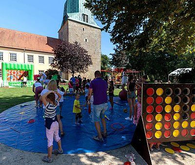 """Beim Sommerfest der Kulturen in Fürstenau gibt es für Kinder viele Aktionen zum Mitmachen. Auf diesem Bild bekommt man einen Einblick von den verschiedenen Spielmöglichkeiten. Vorne rechts im Bild sieht man ein riesengroßes """"Vier gewinnt""""-Spiel stehen. Das Spielbrett besteht aus sieben Spalten (senkrecht) und sechs Reihen (waagerecht) in denen rote und gelbe Spielsteine stecken. Links im Foto, neben dem großen """"Vier gewinnt""""-Spiel ist eine große blaue runde Plane ausgelegt. Auf der Plane stehen Kinder und Erwachsene. Diese spielen mit unterschiedlichen Gegenständen, wie z.B. Keulen und Ringen. Hinter der blauen Plane sieht man eine grüne Rasenfläche. Weiter hinten auf dem grünen Rasen ist eine Hüpfburg aufgebaut. Diese ist mit einem weißen Zaun eingezäunt. Die Hüpfburg ist von außen grün und von innen rot. Hinter der Hüpfburg sieht man die Kirche stehen. Vor dem Kirchturm ist ein Kinderkarussell zu erahnen."""